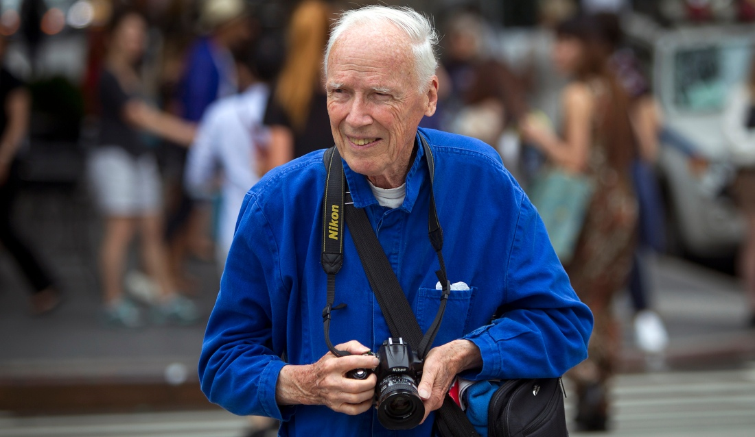 Bill Cunningham crosses the street after taking photos during New York Fashion Week in the Manhattan borough of New York